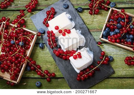 Ice cream with berries. Creamy ice cream and boxes with red currants on an old wooden table. View from above.