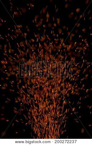 sparks flying upward on a black background