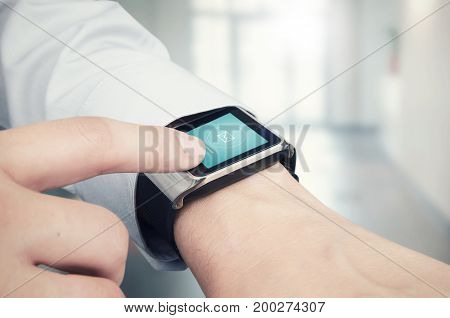 Businessman Checking E-mail On Smart Watch. Office In Background