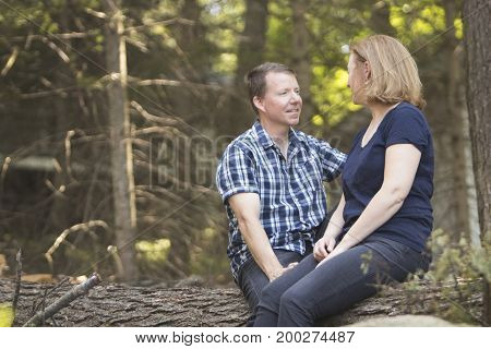 Couple enjoying conversation in outdoors on wooden log