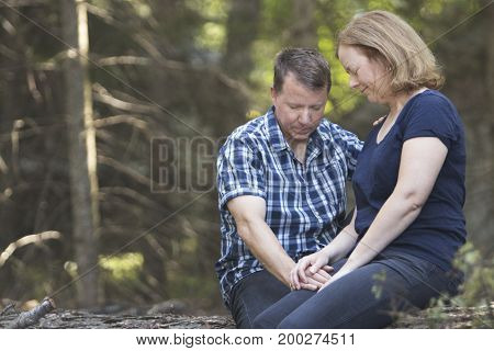 Couple praying together in wooded area and holding hands