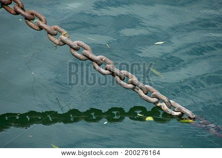 taut metal chain submerged in water with reflection