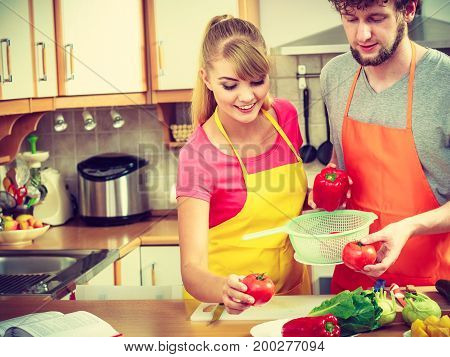 Healthy eating vegetarian food cooking dieting and people concept Happy young couple woman and man having fun in kitchen at home preparing fresh vegetables salad
