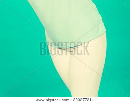 Fashion clothing details concept. Woman white trousers and blue light tshirt blue background.