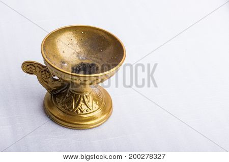 An empty used bronze incense burner on a white surface.