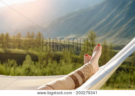 Woman resting in hammock outdoors. Relax View of the mountains