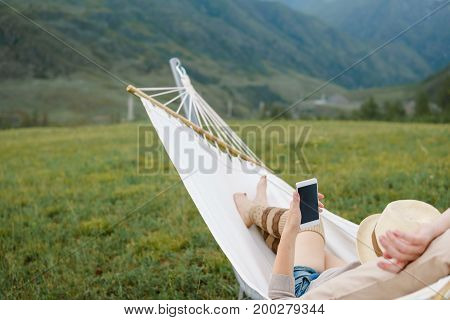 Woman resting in hammock outdoors using smartphone. Relax View of the mountains