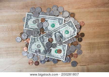 pile of American coins and bills on wooden surface
