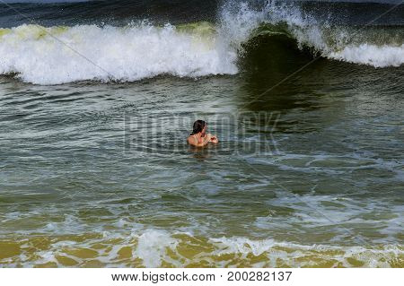 Young Woman Looking At The Wavy Ocean