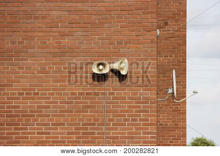 A brick wall of a residential building, two loudspeakers and a satellite dish against the sky.
