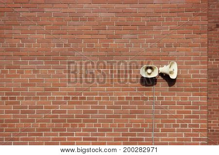 Red brick wall of a residential building and two loudspeakers