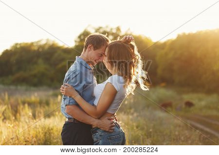 Couple in love. Tenderness and embrace. The guy and the girl look into each other's eyes. Sunset sun over the forest.
