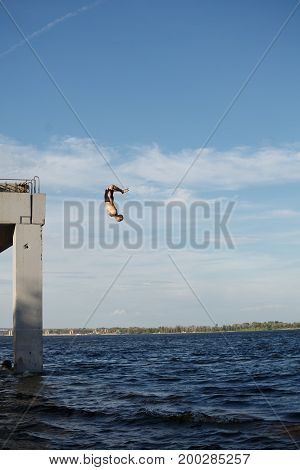 A man is jumping into the sea from a high pier. Adrenaline and extreme. Back flip jump.