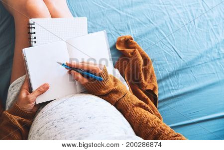 Pregnant woman makes notes and looking at medical documents. Concept of pregnancy health care gynecology medicine. Mother waiting of baby.