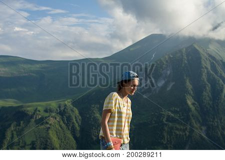 A young girl in a striped yellow T-shirt and a cap in the summer on the fairy-tale mountains and a mysterious misty sky background.