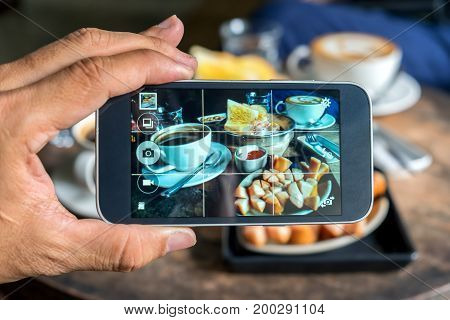 Photos on the smart phone screen simple breakfast egg pans baked bread fried sausage and coffee.