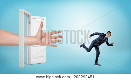 A giant open hand tries to catch a small running businessman through an open white door. Getting away from trouble. Avoid financial crash. Keep independent business.