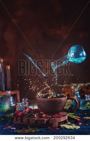 Flying potion bottle with pouring liquid in a magical still life. Brewing enchanted tea. Wooden background with magical supplies. Copy space.