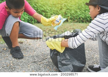 Children hands in yellow gloves picking up empty of Children hands in yellow gloves picking up empty of garbage into bin bag volunteer concept selective and soft focus