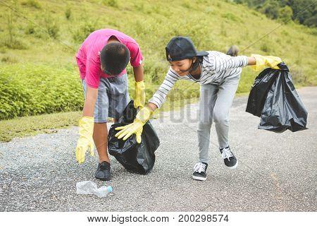 Children hand in yellow gloves picking up empty of bottle plastic into bin bag volunteer concept