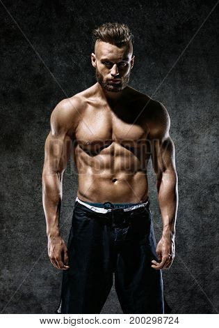 Sporty man with perfect body after training on dark background. Strength and motivation