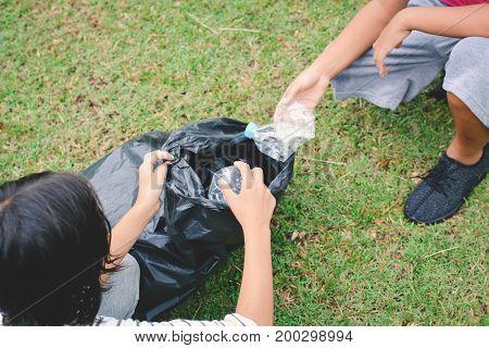 Children picking up empty of bottle plastic into bin bag volunteer concept selective and soft focus