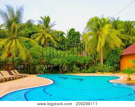 Koh Samui, Thailand - June 27, 2008: Houses, deck chair and beautiful swimming pool with palm tree at Chaweng Buri Resort at Koh Samui, Thailand on June 27, 2008