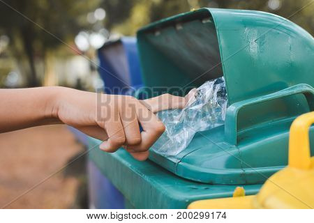 Close up girl hand holding empty bottle into the trash