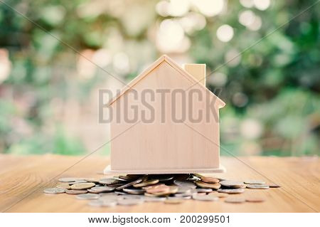 Coins and wood house on table tree bokeh background concept save money for home selective and soft focus vintage tone