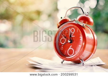 Red alarm clock and money on wood table tree bokeh background