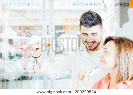 Side view of mature teacher working with young man in classroom and communicating happily.