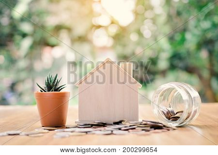Coins and wood house with cactus on table tree bokeh background concept save money for home selective and soft focus vintage tone