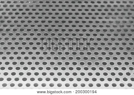 Fabric Texture Close Up of Matalic Silver Perforated Grid to Created A Textured Background.