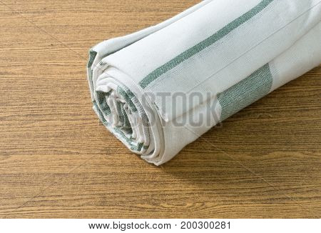 Kitchen Utensil White and Green Napkin Serviette or Kitchen Towel on Wooden Table with Copy Space for Text Decorated.