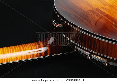 Banjo. Mahogany banjo on a black background.