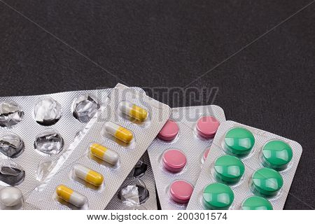 Plateau of black pills on the black background