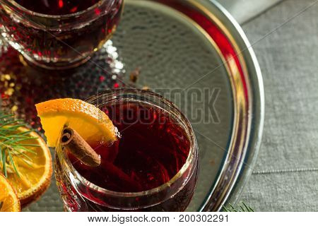 Hot mulled red wine on christmas table decorated by orange slices spices and spruce twigs.