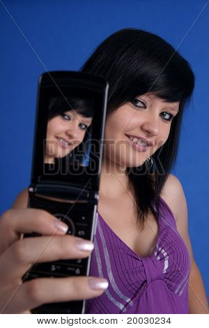 Girl taking autoportrait using mobile phone