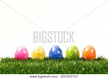 A row of five colorful easter eggs on green grass in Springtime isolated on white background