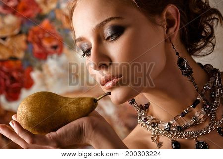 Photo of a beautiful elegant woman holding a pear on her palm.