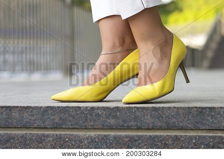 Yellow females shoes. Woman's legs standing at empty street in elegant yellow shoes with stilettos. Silver leg bracelet. Women's fashion