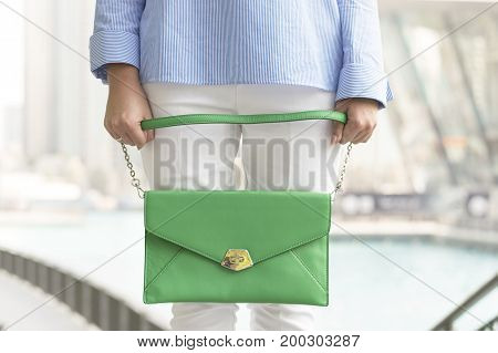 Woman in white trousers and blue shirt holding a green handbag. Stylish woman's clutch. Business and casual fashion. Woman's accessories