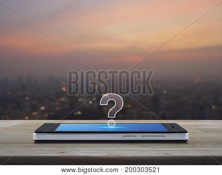 Question mark icon on modern smart phone screen on wooden table over blur of cityscape on warm light sundown Customer support concept