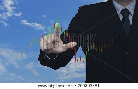Businessman pressing to trading graph of stock market over blue sky with white clouds Business investment concept