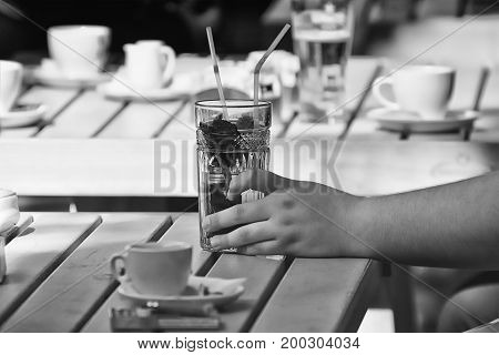 Male hand holding a glass of refreshing drink at an outdoor cafe - B&W