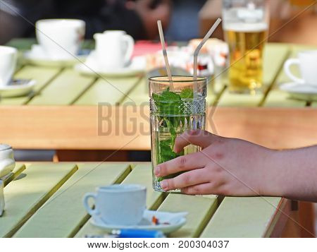 Male hand holding a glass of refreshing mojito drink at an outdoor cafe