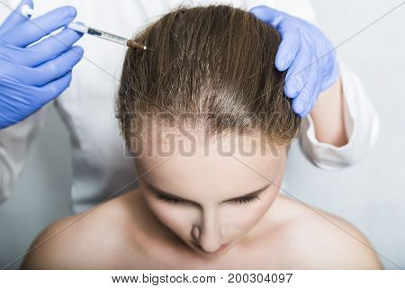 Doctor aesthetician with blue medical gloves makes rejuvenation beauty injections in the head of female patient for hair growth and to prevent boldness.