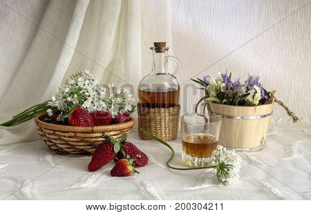 Still life with strawberries, brandy and wild iris on a table close-up