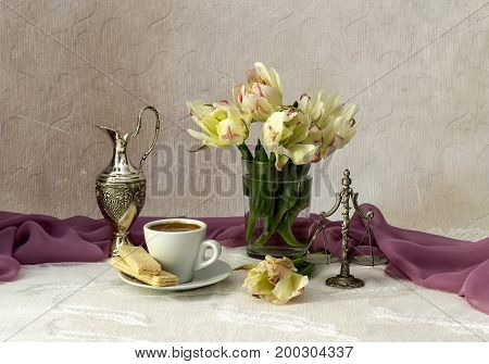 Still life with varietal tulips and a cup of coffee on a table close-up