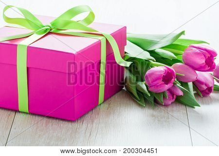 Pink Tulip Flowers and Pink Giftbox on rustic table for March 8 International Womens Day Birthday Valentines Day or Mothers day - Closeup